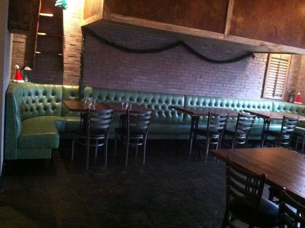 green booths and wooden chairs